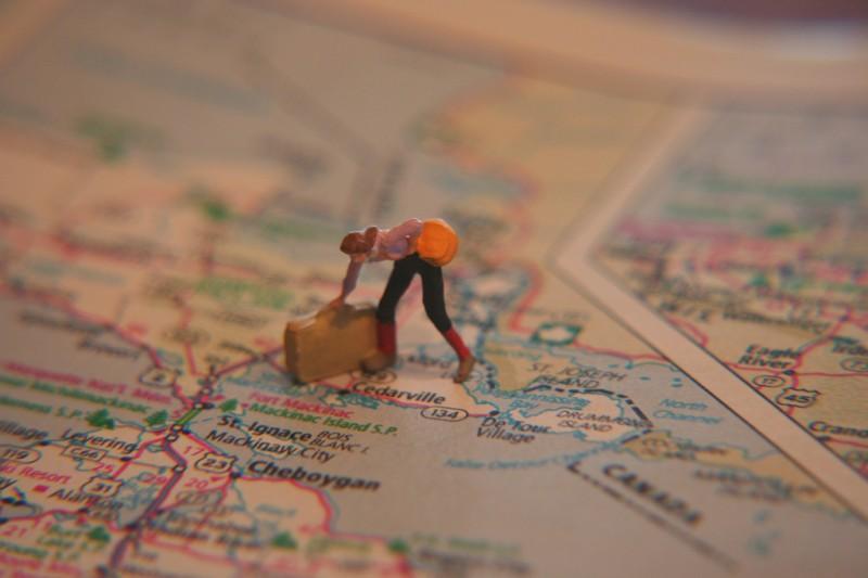 Miniature woman traveler figure standing on paper map